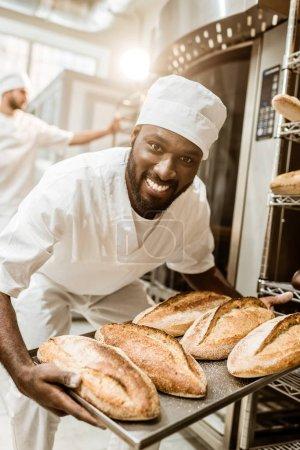 Photo pour Heureux boulanger afro-américain prendre pains du four à la fabrication de cuisson - image libre de droit