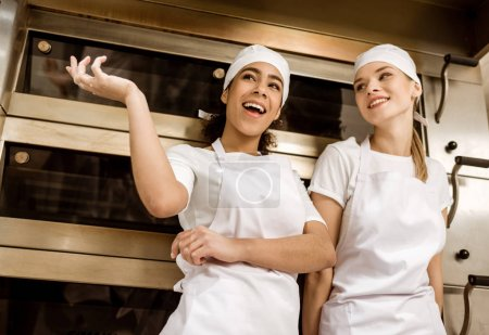 happy female bakers chatting at baking manufacture
