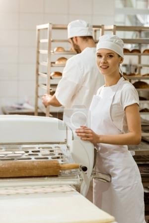 female baker with industrial dough roller at baking manufacture