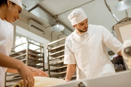 Photo for Young confident bakers working with industrial dough roller at baking manufacture - Royalty Free Image