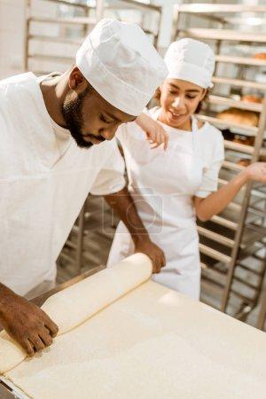 Photo pour Boulangers afro-américains travaillant avec rouleau de pâte industrielle fabrication de cuisson - image libre de droit