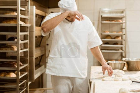 exhausted baker working with raw dough at on baking manufacture and wiping sweat
