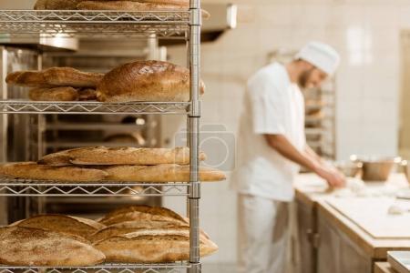 Photo pour Étagères avec du pain frais et boulanger flou sur le fond à la fabrication de cuisson - image libre de droit