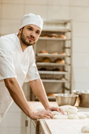 handsome young baker with raw dough at workplace on baking manufacture