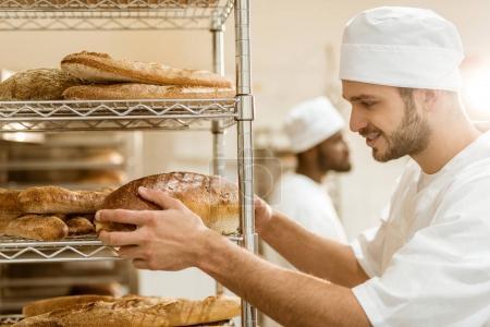 Photo for Handsome smiling  baker putting fresh bread loaf on shelf at baking manufacture - Royalty Free Image