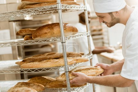 handsome young baker putting fresh bread loaf on shelf at baking manufacture