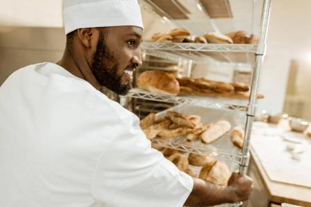 Photo for Happy african american baker driving shelves of fresh bread on baking manufacture - Royalty Free Image