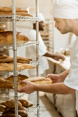 Photo for Handsome baker putting fresh bread loaf on shelf at baking manufacture - Royalty Free Image