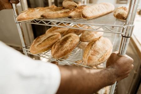 Photo pour Plan recadré de boulanger conduisant des étagères de pain frais sur la fabrication de la cuisson - image libre de droit
