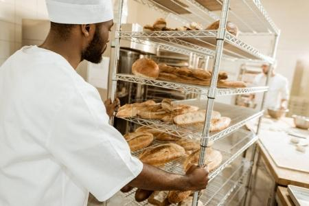 Photo for Baker driving shelves of fresh bread on baking manufacture - Royalty Free Image