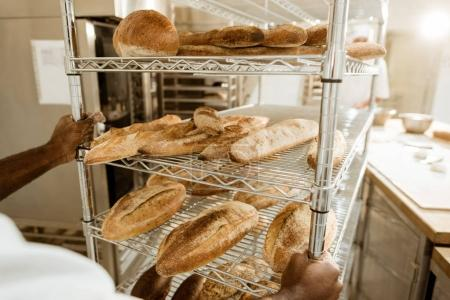 cropped shot of baker driving shelves of fresh bread on baking manufacture