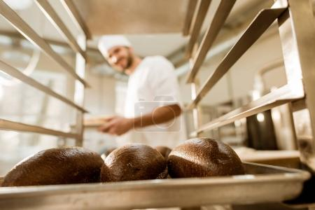 Photo for Happy baker looking at fresh loaves of bread on baking manufacture - Royalty Free Image