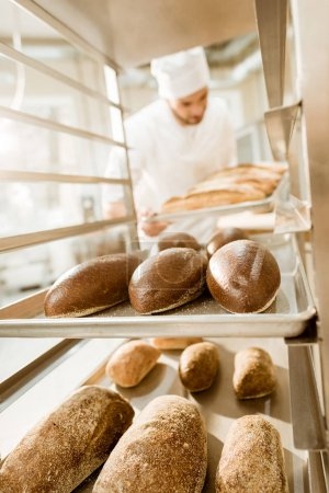 baker putting trays of fresh bread on stand at baking manufacture