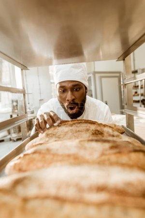 shocked african american baker looking at fresh loaves of bread on baking manufacture