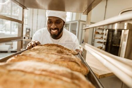 Photo pour Souriant pâtissier afro-américain regardant des pains frais sur la fabrication de la cuisson - image libre de droit