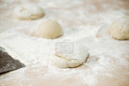 close-up shot of dough ball on table spilled with flour