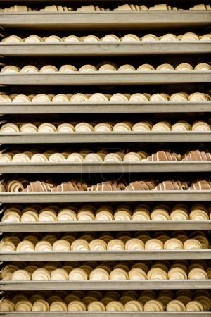raw croissants on shelves in industrial oven