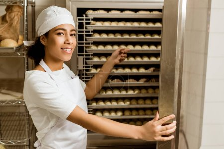 Smiling female baker pointing at dough inside of i...