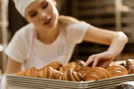 close-up shot of young female baker doing examination of freshly baked croissants on baking manufacture