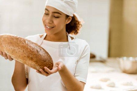 Photo pour Souriant boulanger femelle tenant pain frais sur la fabrication de la cuisson - image libre de droit