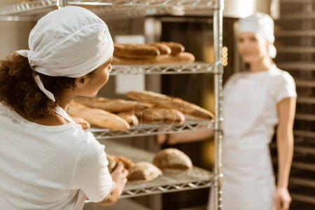 Photo pour Boulangeries féminines travaillant ensemble à la fabrication de cuisson et bavardage - image libre de droit