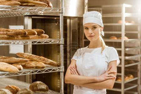 Photo for Young female baker with crossed arms near shelves with freshly baked bread on baking manufacture - Royalty Free Image