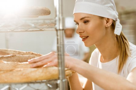 young female baker doing examination of freshly baked bread loaves on baking manufacture