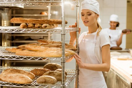 Photo for Beautiful female baker standing near shelves with fresh loaves of bread at baking manufacture - Royalty Free Image