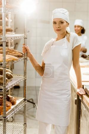 young female baker standing near shelves with fresh loaves of bread at baking manufacture