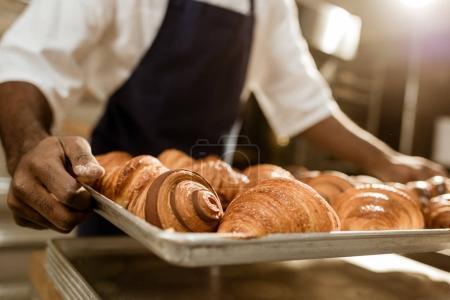 plan recadré de la plaque de maintien boulanger avec des croissants sur la fabrication de cuisson