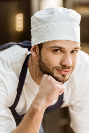 close-up portrait of handsome young baker looking at camera on baking manufacture