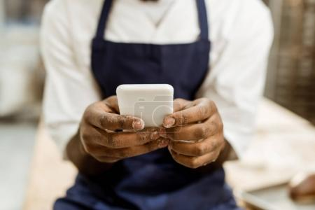 cropped shot of african american baker with hands covered in flour using smartphone