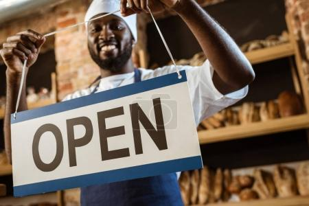 happy african american baker holding open sign at pastry store