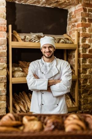 handsome smiling baker with crossed arms standing at pastry store