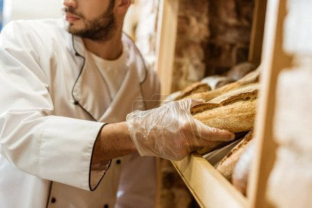 cropped shot of baker putting loaf of bread on shelf at store