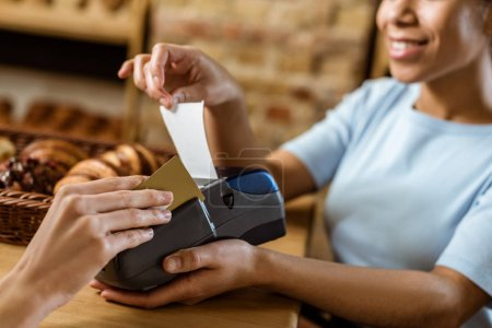 close-up shot of smiling cashier with pos terminal receiving purchase from client at pastry store