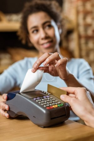 cropped shot of cashier with pos terminal receiving purchase from client at pastry store