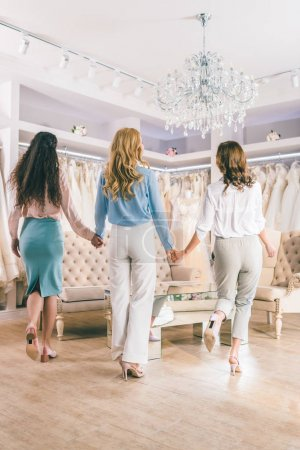 Rear view of female friends holding hands in wedding salon