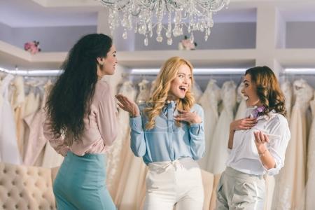 Photo pour Jeunes femmes s'amuser dans la boutique de mode de mariage - image libre de droit