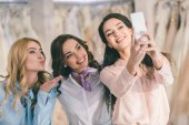 Young smiling bride and bridesmaids taking selfie on smartphone in wedding atelier