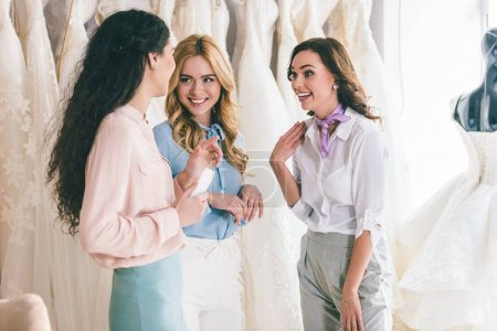 Female friends chatting about dresses in wedding fashion shop