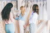 Happy bride and bridesmaids trying on dresses in wedding atelier