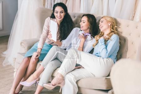 Happy young women taking selfie in wedding salon