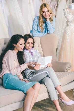 Happy bride and bridesmaids looking at tablet in wedding atelier