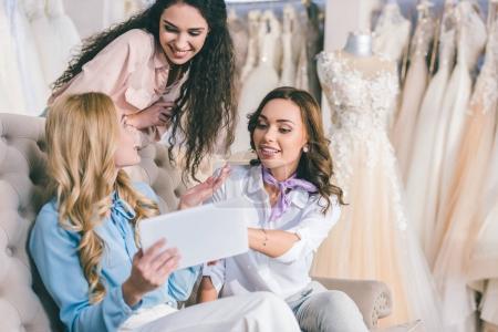Photo pour Jolies femmes choisir robe de mariée et regardant la tablette dans l'atelier du mariage - image libre de droit