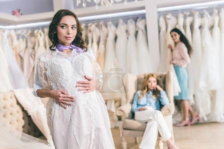 Bride with friends choosing dresses in wedding fashion shop