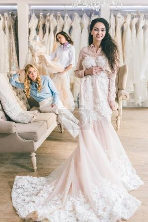 Young bride and bridesmaids holding dresses in wedding atelier