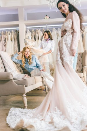 Young smiling bride and bridesmaids with dresses in wedding fashion shop
