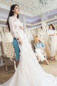 Bride with lace dresses and bridesmaids in wedding atelier