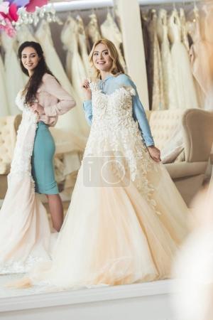 Brides holding lace dresses in wedding salon